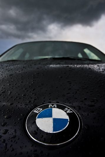 Photo of BMW emblem with dark skies over head.